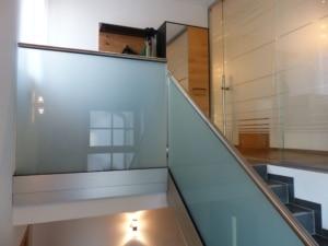 glasraumteiler mit schiebetür und glasgeländer aus oö